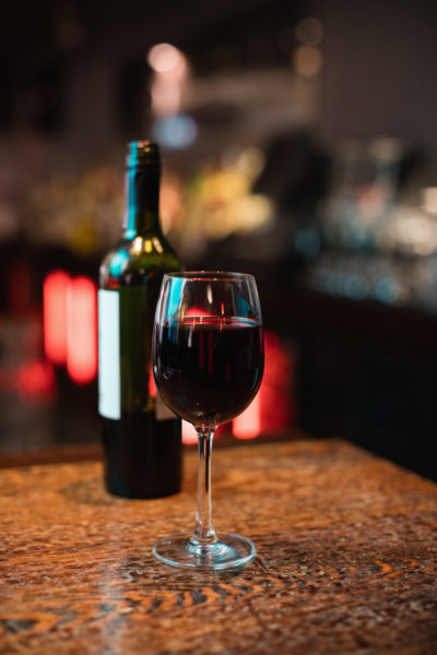 Close-up of red wine glass on bar counter at bar